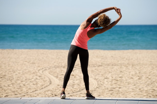 A person in a pink tank top stretches on the boardwalk of a beach. Stretching isn't just for people who practice yoga, and will probably continue to be a fitness trend in 2020.
