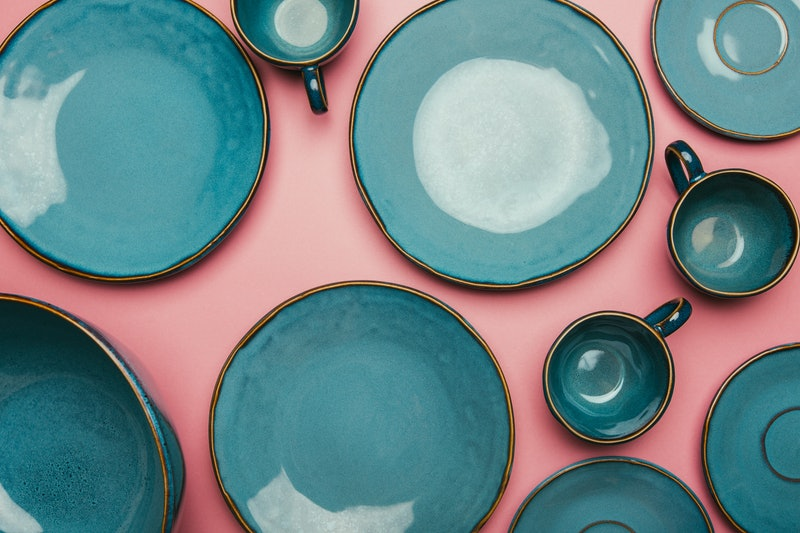 A series of empty blue ceramic plates on a pink background.  Intermittent fasting, where food is restricted to various times of day, has been touted as a health miracle but has side effects, experts say.