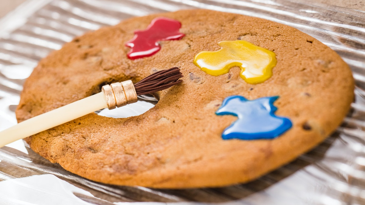 A paint brush sits on top of a artist palette-shaped cookie with colorful icing at Epcot's Internati...