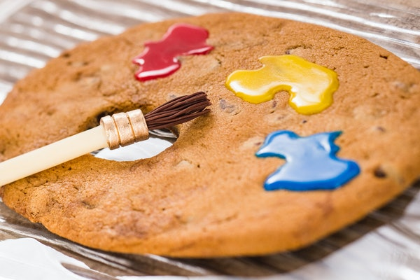 A paint brush sits on top of a artist palette-shaped cookie with colorful icing at Epcot's International Festive of the Arts.