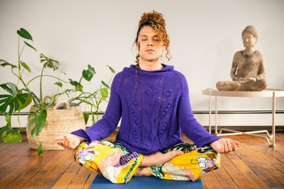 A genderfluid person meditating. Meditating wherever you are and whatever you're doing might be a cool emerging wellness trend of 2020.