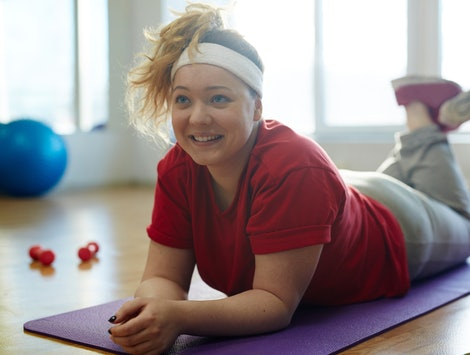 A person in a red t-shirt and white sweatband lays on her purple yoga mat, looking up and smiling. Working out in the morning can help you wake up.
