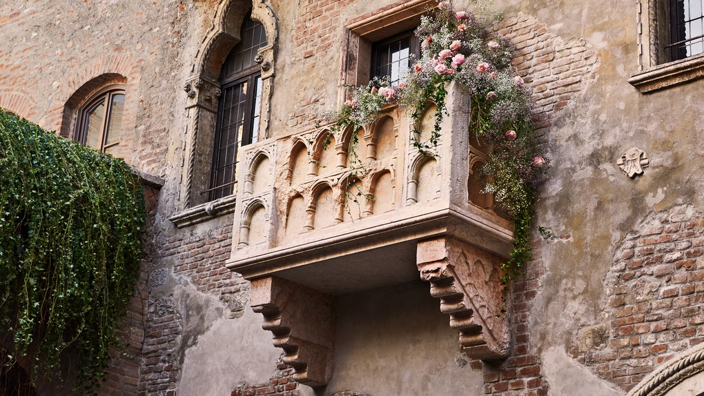 Juliet's balcony covered in pretty flowers overlooks Verona at the 'Romeo and Juliet'-inspired house on Airbnb.
