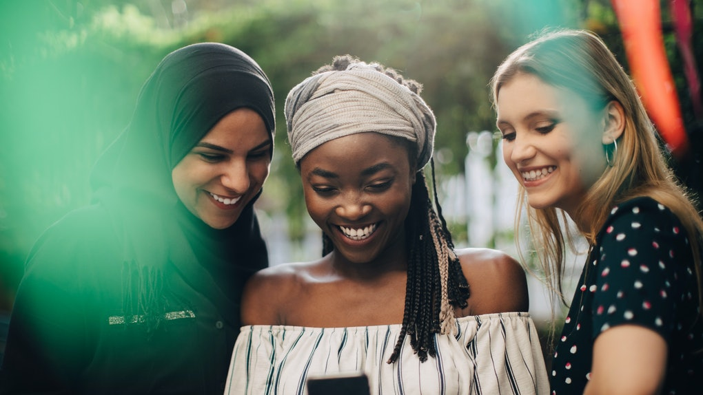 Three friends with headscarves looking at phone, taking selfie
