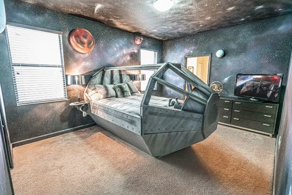 A spaceship bed sits in the center of a 'Star Wars'-themed Airbnb bedroom with galaxy painted walls.