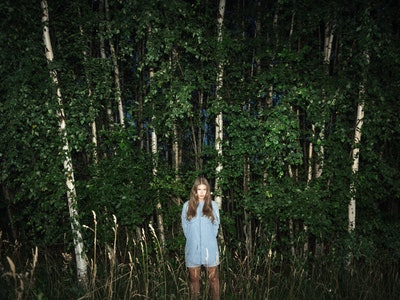 Woman standing alone in woods