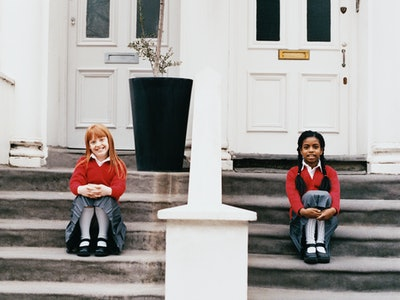 Two girls sit on adjacent stoops in front of their houses