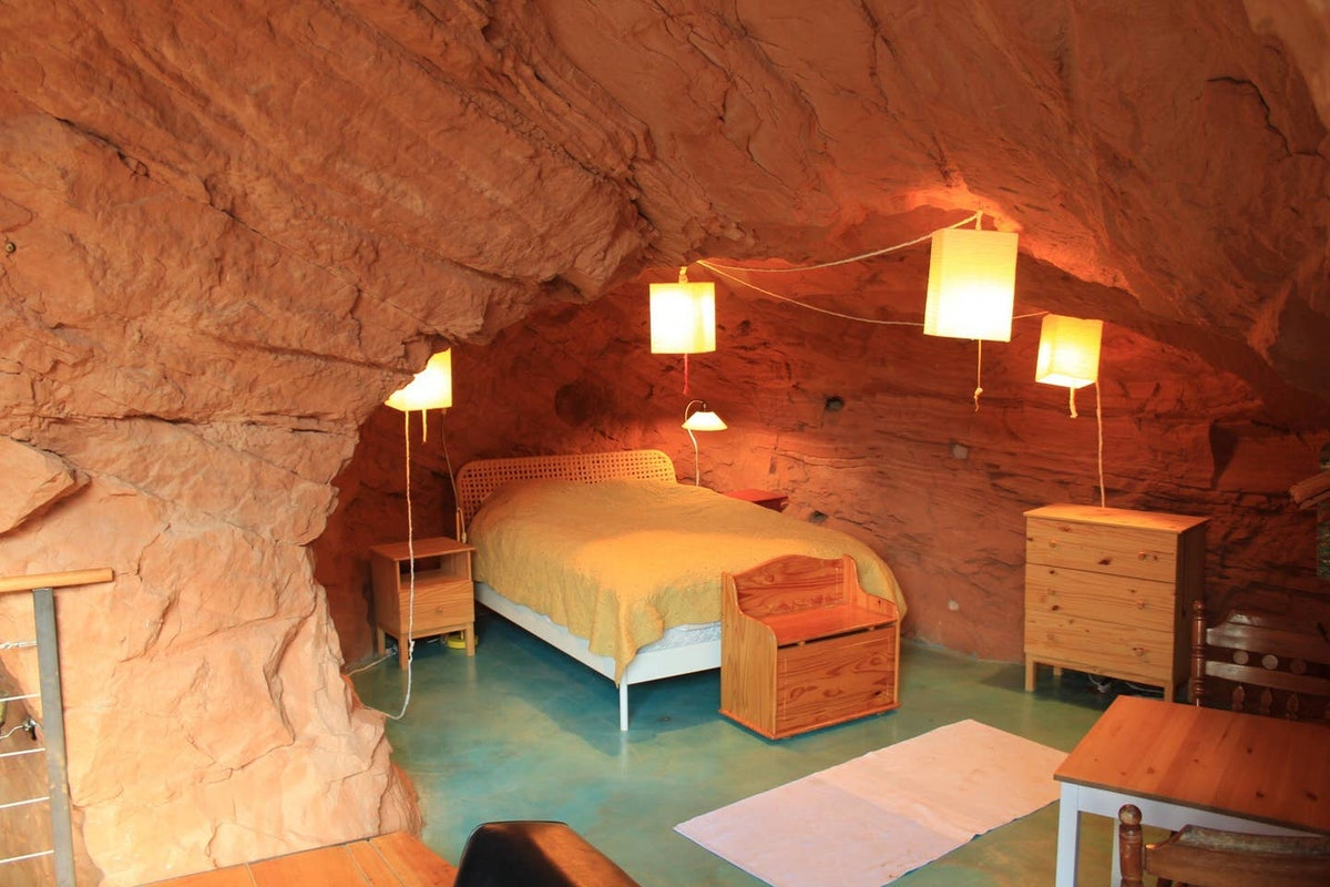 A bedroom in a cave home on Airbnb has a bed, wood furniture, and hanging lanterns.