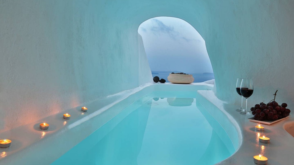 Candles and wine surround a jacuzzi in a cave home in Santorini on Airbnb.