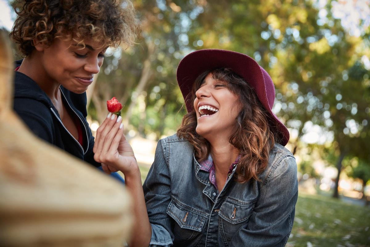 Girlfriends having strawberry on picnic
