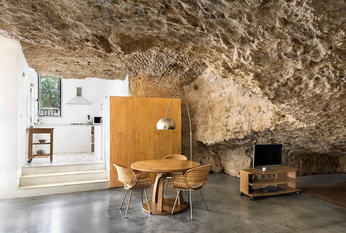 A dining table and TV both fill up the space in an open cave home on Airbnb.
