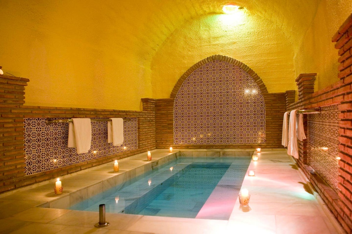 Candles surround a Hammam Arab Bath in a cave home on Airbnb.