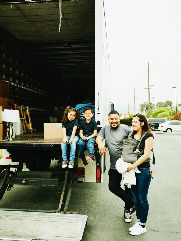 A family, including a baby-wearing mother, stand beside a moving truck