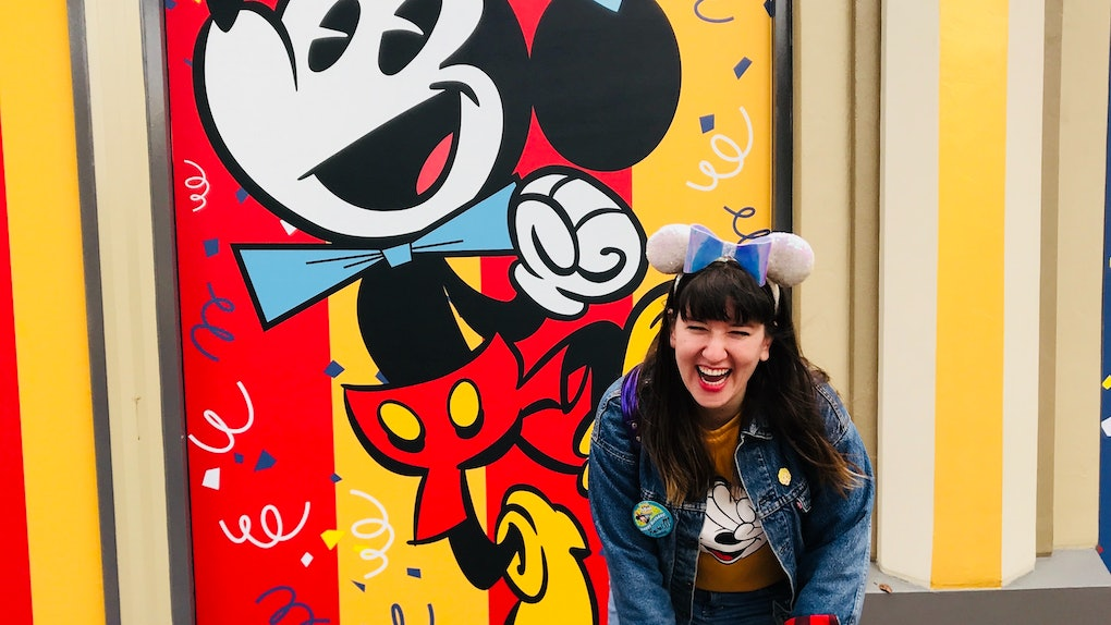 A woman in Mickey ears laughs in front of a Mickey birthday wall at Disneyland.