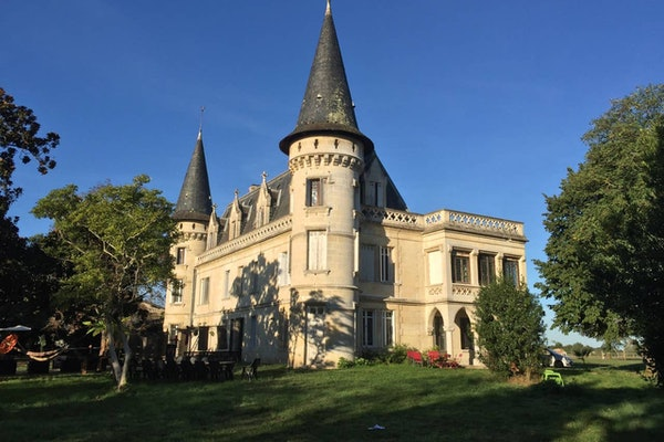 Trees and green grass surround a beautiful castle that's listed on Airbnb in France.