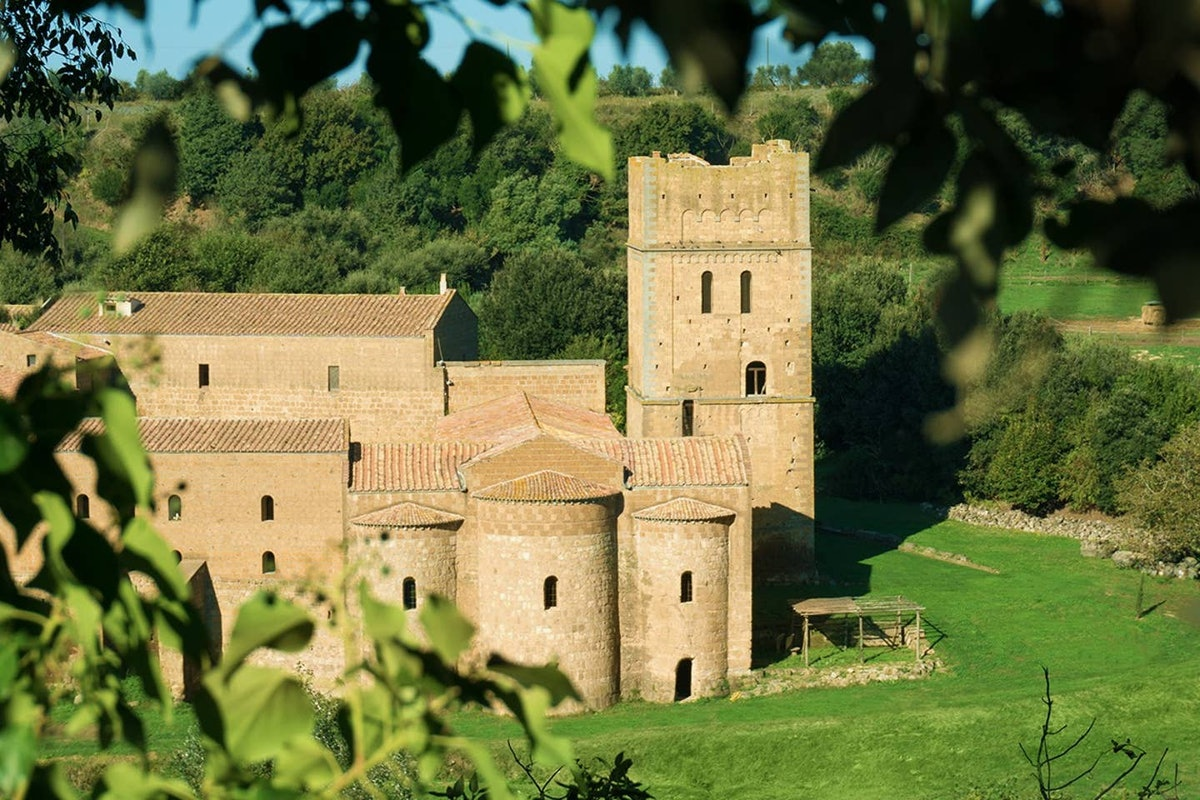 A medieval castle in Italy that's listed on Airbnb is surrounded by greenery.