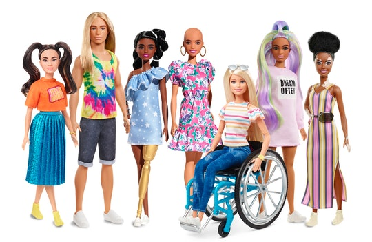 a collection of Barbies. Left to right: Barbie with brunette pigtails, shorter stature, long haired Ken in a tie dye shirt, Barbie with a prosthetic leg,  a Barbie without hair, a Barbie in a wheelchair, a Barbie with vitiligo.