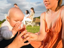 A mother in Agen, France, allows her baby to sniff her wine glass