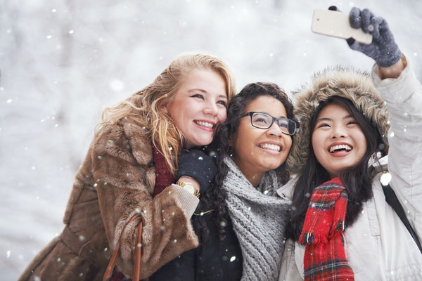 Three young female friends happy in snow, winter