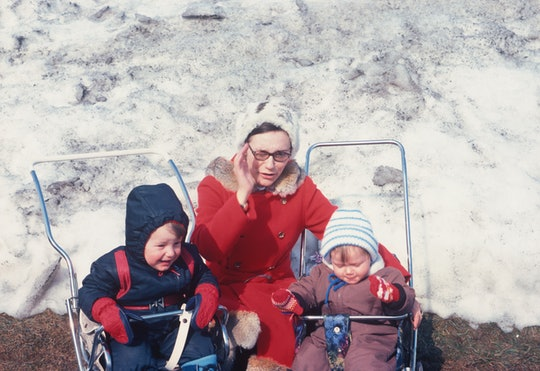 A vintage mother with two children in strollers in front of snow