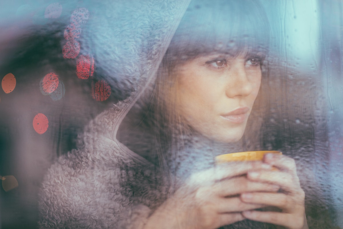 Young woman with coffee looking out window during rain