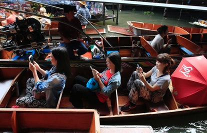 Tourists looking at their mobile phones instead of the passing sights at the famous Damnoen Saduak F...
