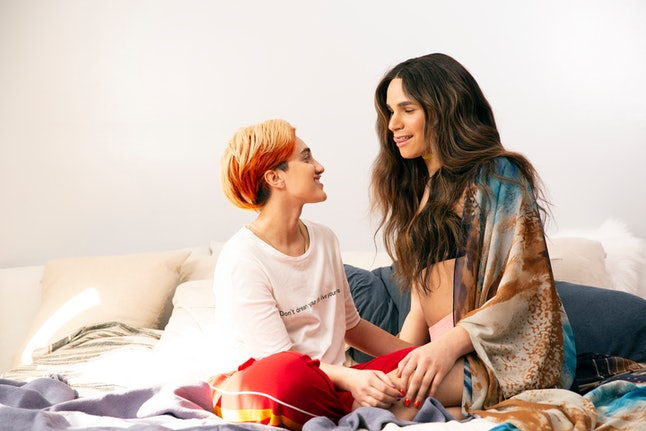 A transmasculine gender-nonconforming person and transfeminine non-binary person sitting on a bed smiling. Being selfish can be a great way to treat yourself and your friends well, even if it seems counterintuitive at first.