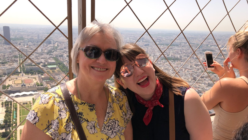 A woman and her mom pose for a picture in Paris on a sunny day.