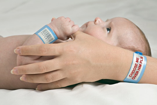 a mother's hands hold a newborn with hospital bracelets on