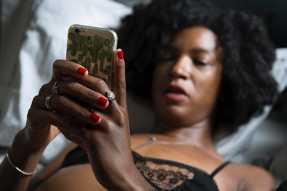 A woman in lingerie looks at her phone. Sexting can trigger the body's limbic system.