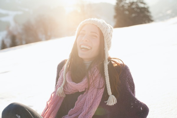 Young woman laughing in the sunlight & snow
