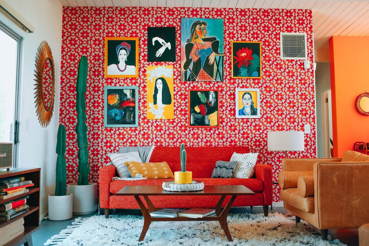 The living room in a Mid-Century Palm Springs home has colorful furniture and painting on the wall.