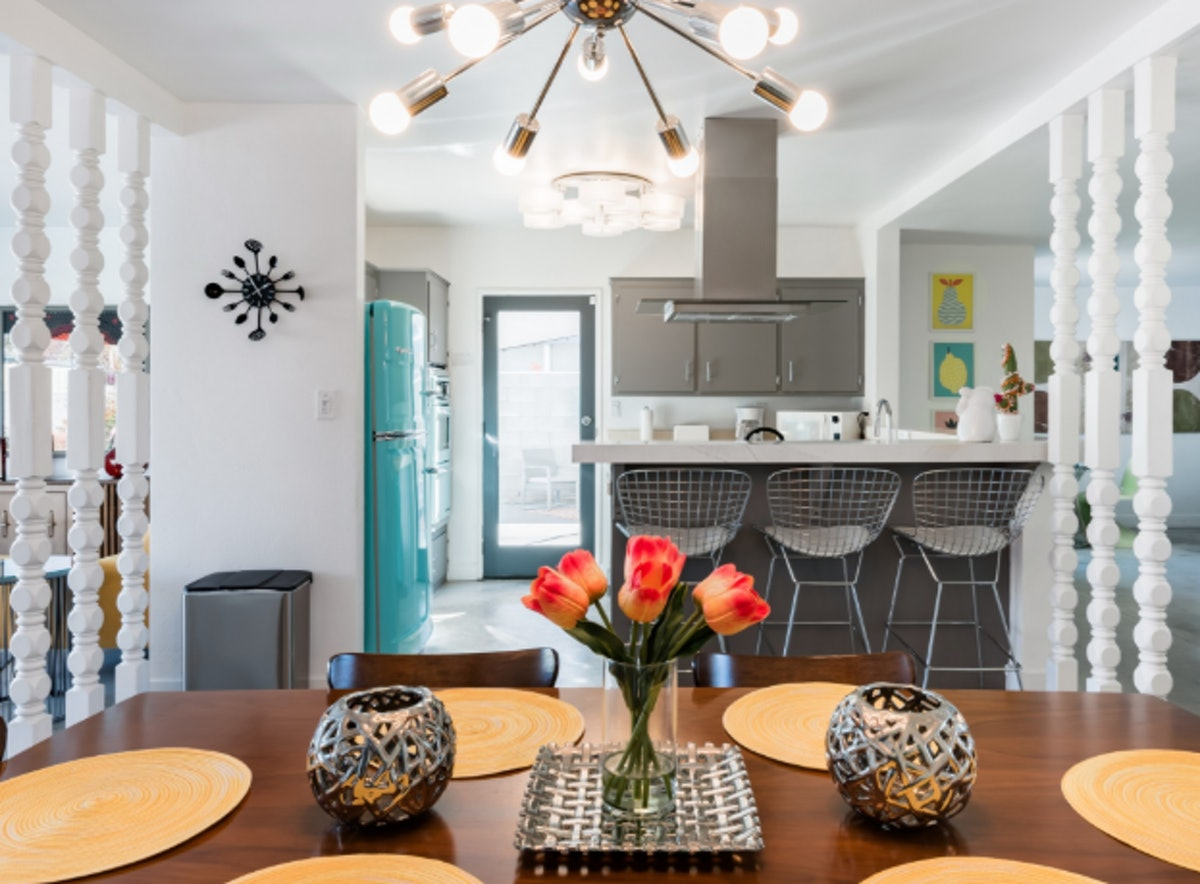 The kitchen in a mid-Century home in Palm Springs has a retro teal refrigerator, wooden table, and modern lighting fixtures.