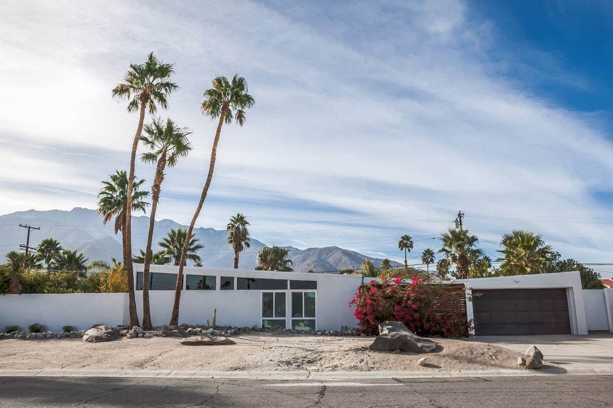 A mid-century modern home in Palm Springs has palm trees in the front yard and mountains behind it.