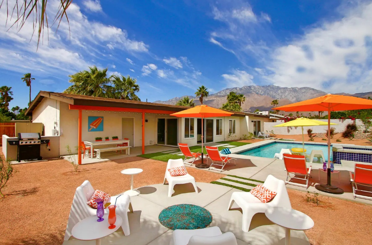 A backyard pool area in Palm Springs has orange lounge chairs and umbrellas.