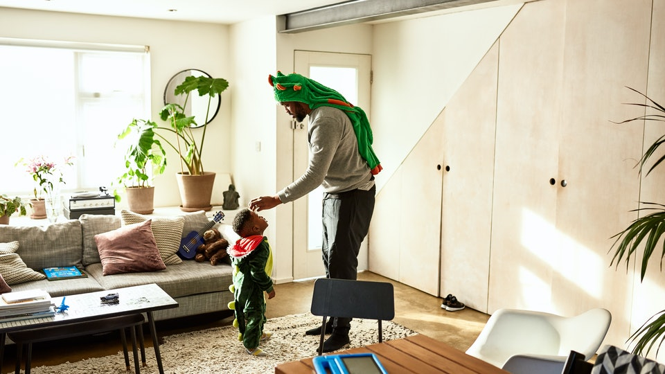 Dad in dinosaur plays with son in dinosaur costume