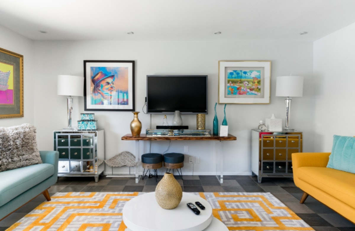 The living room in this Palm Springs home is decorated with colorful, retro furniture and old Hollywood art.