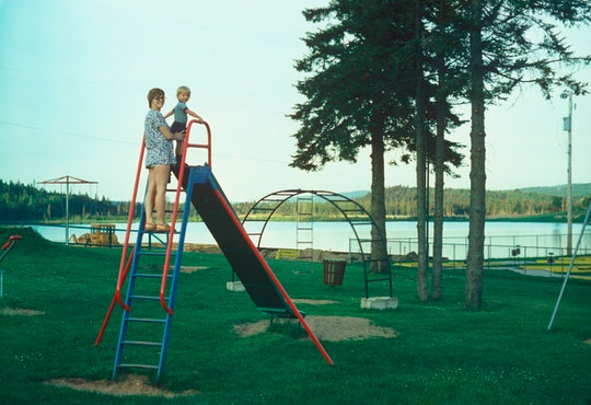 A mother standing at the top of a slide with her young son.