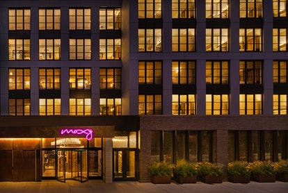 The exterior of the Moxy East Village has a neon pink sign and greenery.