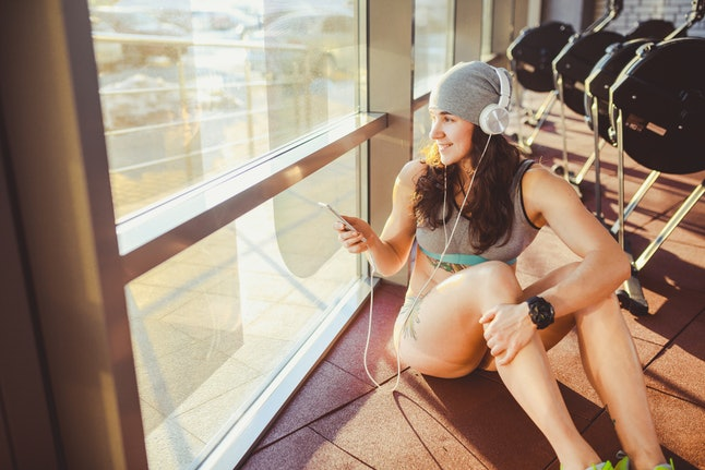 A person wearing a beanie and workout gear looks out the window of her gym while smiling and listening to music on her phone. Giving yourself rewards for small successes can be an important part of forming a consistent fitness habit.