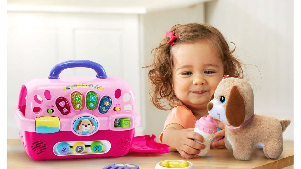a toddler girl playing with a vtech care for me learning carrier