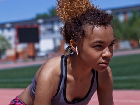 A young Black woman wearing a sports bra and shorts listens to music while preparing to sprint. Listening to fitness podcasts can be an awesome way to engage with your body and mind this year.