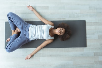 A person lays cross-legged with her palms out on a yoga mat. Personalizing your exercise goals is an important part of making working out a consistent habit.