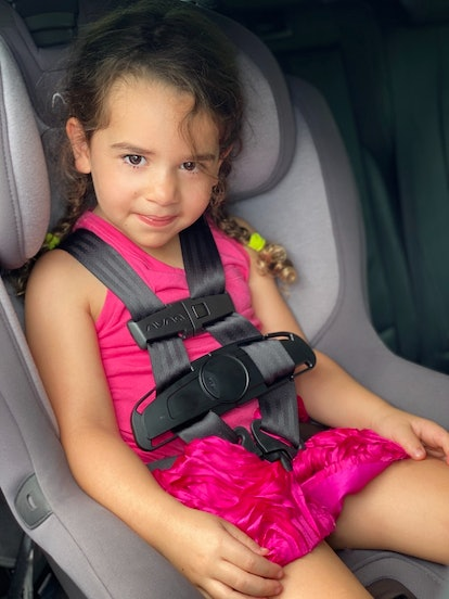 A young girl smiles in her car seat, equipped with the Car Seat CoPilot hot car safety device.