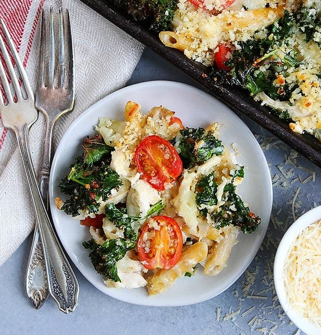 Sheet pan pasta bake recipe from Two Peas & Their Pod includes chicken, penne pasta, and cherry tomatoes for a quick and healthy meal
