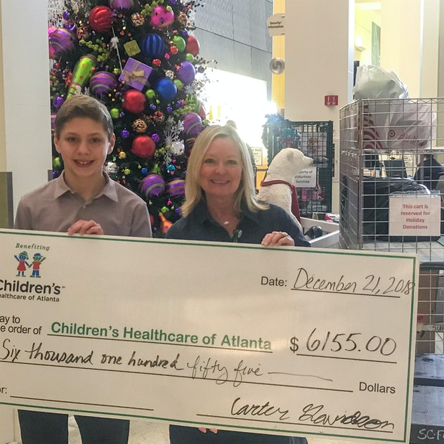 A picture of Carter Davidson offering a woman a huge check.