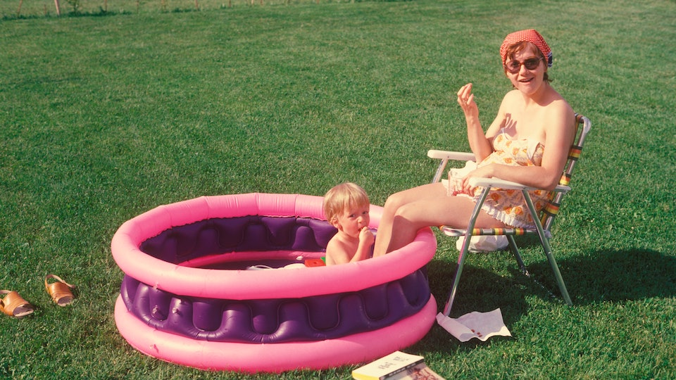 Mother sits with legs in paddle pool, where child plays