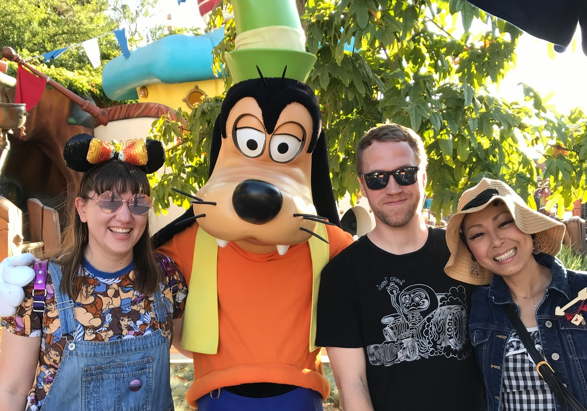 A group of friends poses for a picture with Goofy at Disneyland.