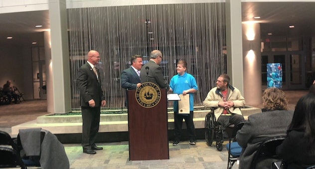 "A picture of young Josh Cudzey being awarded the ""Citizen of the Day,"" award."