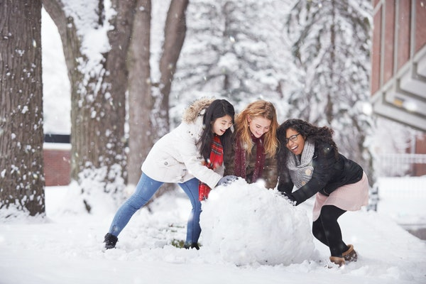 Multi-ethnic female friends building snowman